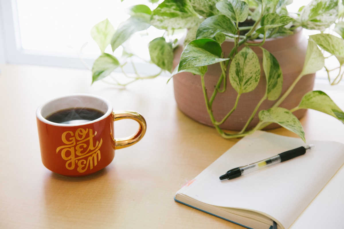 paper journal for manifestation next to a cup of coffee and an indoor plant